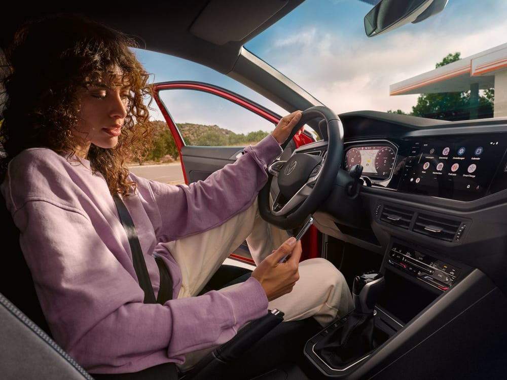 TA0017-taigo-interior-woman-sitting-on-drivers-seat-looking-at-phone